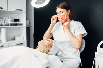 Beautician watches on patient face in mask
