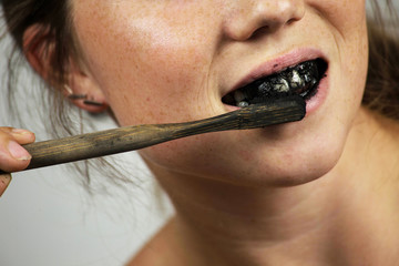 young woman brushing her teeth with a black tooth paste with active charcoal, and black tooth brush on white background for Teeth whitening