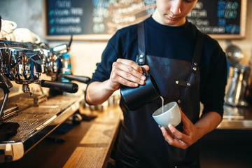 Barista pours cream into the cup of coffee