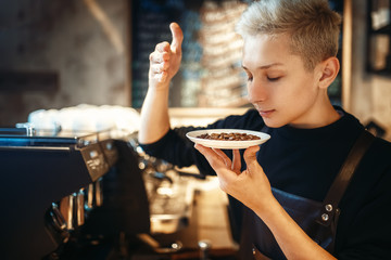 Young male barista sniffs fresh coffee beans