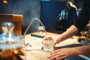 Male barista pours filtered water into the glass