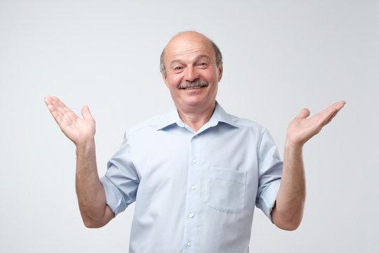 Indoor portrait of confused senior man in blue shirt showing I have no idea gesture