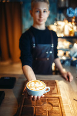 Male barista shows cup of coffee with foam drawing