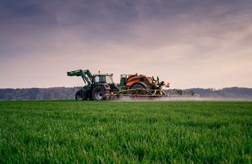 Ackerbau, Landwirt spritzt am Abend sein Getreidefeld, Sprühnebel