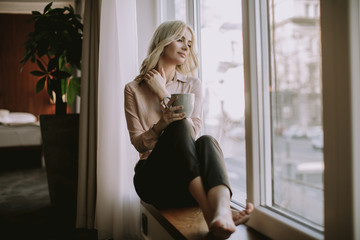 Blonde young woman drinking coffee by window