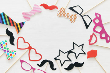Top view image of funny and colorful photo booth props for party over white background.
