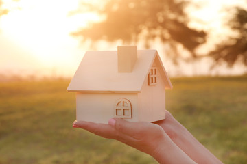 Image of woman holding small wooden house outdoors at sunset light.
