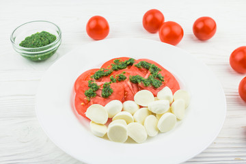 caprese with tomatoes and mozzarella and pesto sauce, on a wooden background