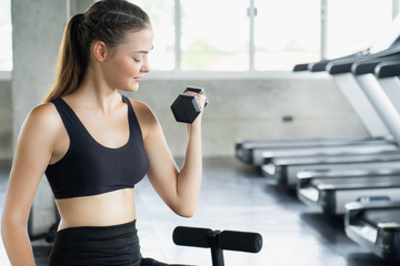 Muscular young woman with beautiful  body doing exercises with dumbbell. Sporty girl lifting weights in gym.