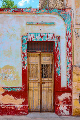 Colorful grunge around broken down door with wrought iron accents and locked bars in front on street in Merida Yucatan Mexico