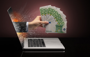 Hand with cash coming out of a laptop with sparkling effects