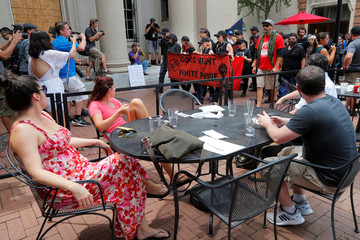 A group wearing anti-fascist attire pass outdoor restaurant diners on the Downtown Mall in Charlottesville