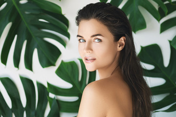 Portrait of young and beautiful woman with perfect smooth skin in tropical leaves