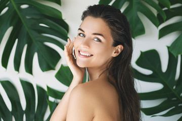 Portrait of young and beautiful woman with perfect smooth skin in tropical leaves Wall mural