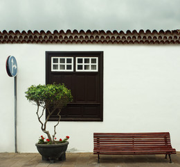Beautiful detail of a typical facade of a small house with a big window a plant with flowers, tiles roof, a bench and a road sign in Garachico, Tenerife, Canary Island