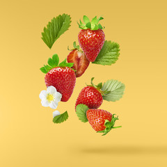 Photo sur Toile Dans la glace Flying Fresh tasty ripe strawberry with green leaves