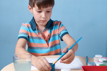 European boy spending time painting with colorful watercolors at home.