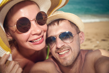 Young couple is taking selfie photo on the beach. Focuse on a girl..