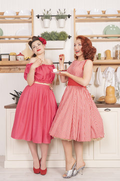 Pretty cute joyful ladies wearing vintage clothes and having fun in their white kitchen