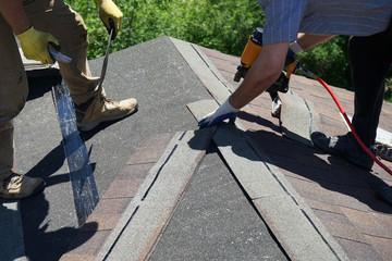 Roofer builders installing Asphalt Shingles or Bitumen Tiles on a roof of a new house.