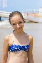 Pretty girl in bikini on the beach smiling to the camera