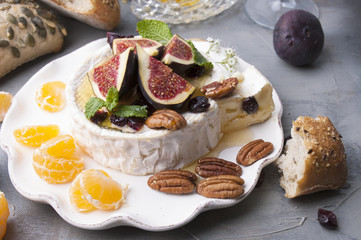 Cheese with white mold and figs, honey and nuts. Autumn sweets and fruits and wine. Delicious food for dinner. Top view