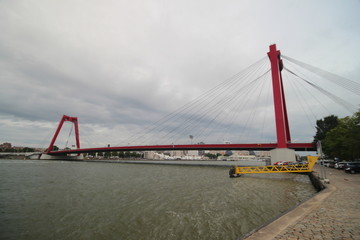 skyline of river Nieuwe maas in the middle of Rotterdam with the willemsbrug bridge with red color.
