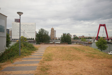 Remains of land abutment of the railbridge over river nieuwe maas in Rotterdam, which is demolished after tunnel were openend, with Willemsbrug bridge on the right.