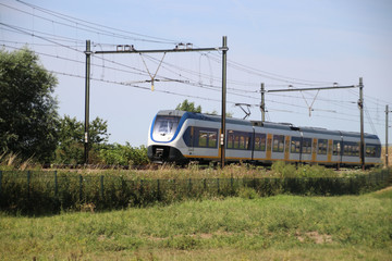 Local commuter train on the track at Moordrecht heading to Rotterdam in the Netherlands.