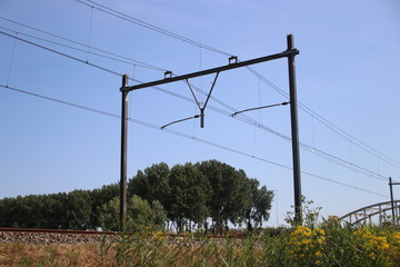 Railroad track at Moordrecht heading to Rotterdam in the Netherlands with electricity wires with poles