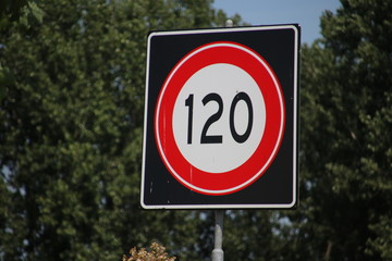 Speed sign along the motorway in the Netherlands with speed limit of 120 kilometers .