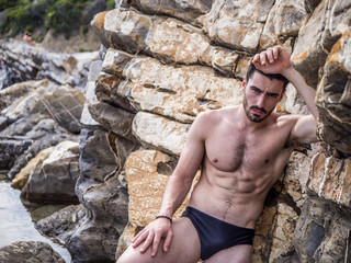Handsome muscular young man standing on a rocky beach, relaxed, shirtless, looking at camera