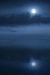 Beautiful night time aerial view of large Blue Moon and Ocean waters