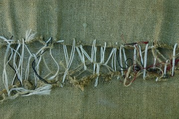 part of a green old ragged fabric sewn with gray thread