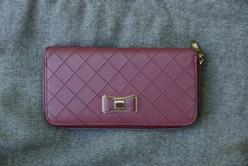 large red leather purse on gray fabric
