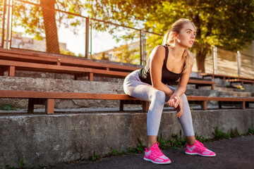 Young woman athlete having rest after running on sportsground in summer.