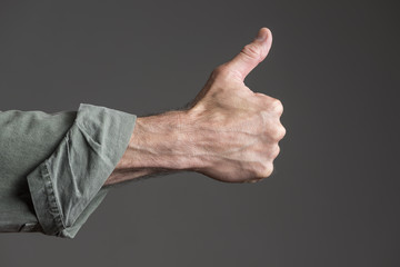 Isolated thumbs up.  Man's hand.  Green canvas shirt.  Grey backgound.  Back of hand facing the camera.  Cuff rolled up.