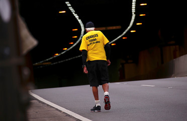 A participant wearing a shirt that stating he has run in 48 races, walks towards a tunnel at the start of the annual City to Surf fun race from Sydney's CBD to the iconic Bondi Beach