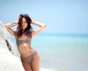 Young beautiful sexy woman posing in swimsuit bikini near white rocks on beach sea shore