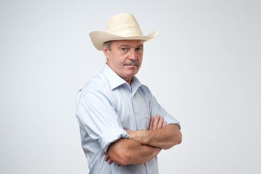 Mature man adjusting his cowboy hat and looking at camera while standing against grey background