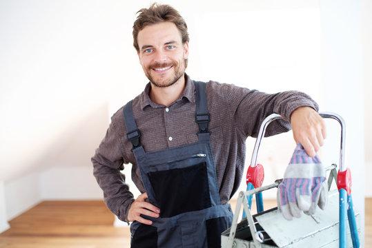 Handwerker sympathisch lächelnd in einem Gebäude