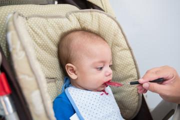 Blue eyed baby boy eating - In baby stroller