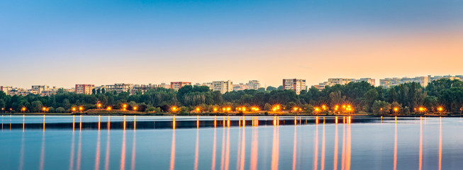 Fotomurales - Panoramic view of Tomis Nord neighborhood skyline across Tabacariei lake, at dusk, in Constanta, Romania