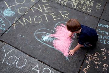Thompson draws the shape of a heart on the sidewalk outside of Foggy Bottom rail station ahead of a planned demonstration by white nationalists in Washington