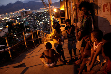 Kids chat as they wait for the distribution of kites with LED lights during the Pipas pela Paz (Kites for Peace) event in the Alemao slums complex in Rio de Janeiro