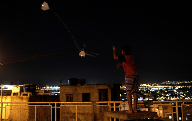 A boy flies a kite with LED lights during the Pipas pela Paz (Kites for Peace) event in the Alemao slums complex in Rio de Janeiro
