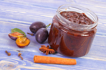 Plum marmalade or jam in glass jar, fruits and spices on boards, sweet dessert concept