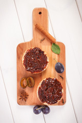 Sandwiches with plum marmalade or jam on wooden cutting board, breakfast concept