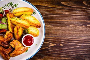 Roast chicken wings, chips and vegetables
