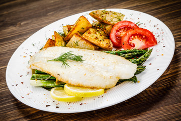 Fish dish - fried fish fillet with fried potatoes and vegetables